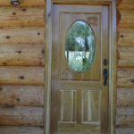 Custom cherry enrtry door with chickadees and pinecones carved in